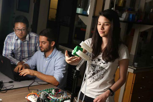 Ph.D. students Benjamin Shih and Dylan Drotman monitor a computer while Ph.D. student Adriane Minori gets ready to remove a 3D-printed object from the soft robotic gripper.