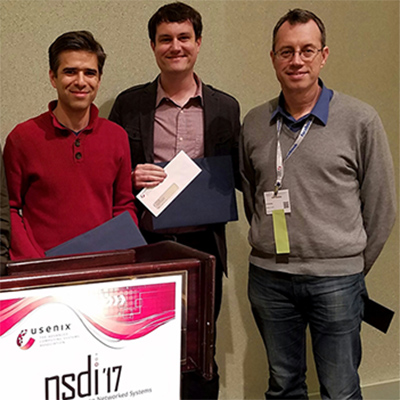 CSE Prof. George Porter (center) and co-authors Rodrigo Fonseca (left) and Ion Stoica accept their Test of Time Award at NSDI 2017 in Boston.