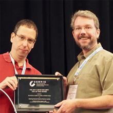 CSE prof. Geoffrey Voelker (right) accepts USENIX Security Test of Time Award on Aug. 16.